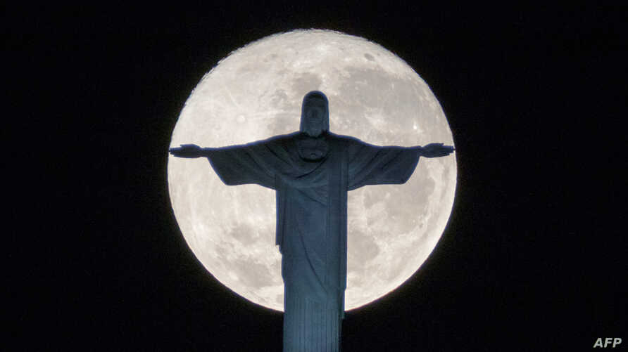 The silhouette of the statue of Christ the Redeemer atop Corcovado hill stands out against the full moon in Rio de Janeiro, Brazil, on July 19, 2016.