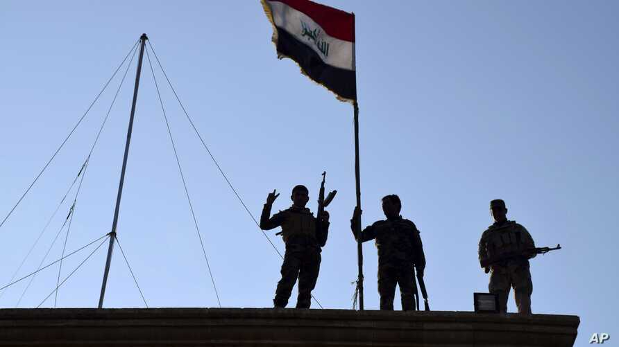Iraqi soldiers plant the national flag over a government building in Ramadi as security forces advance their position in northern Ramadi, 70 miles (115 kilometers) west of Baghdad, Iraq, Dec. 21, 2015.
