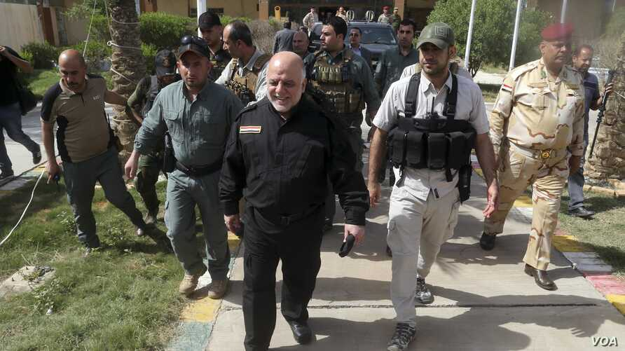Iraq Prime Minister Haider al-Abadi, center, smiles as he leaving the operations centre outside Fallujah, Iraq, June 1, 2016.