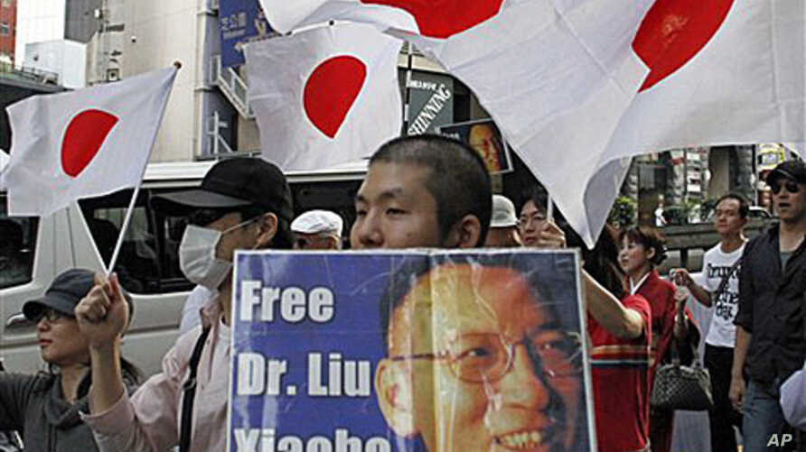 """A Japanese protester holding a placard with a message reading, """"Free (Nobel Peace Prize winner) Dr. Liu Xiaobo,"""" marches down streets in central Tokyo as an estimated  2,500 protesters take to the streets in a protest against China, 16 Oct 2010."""