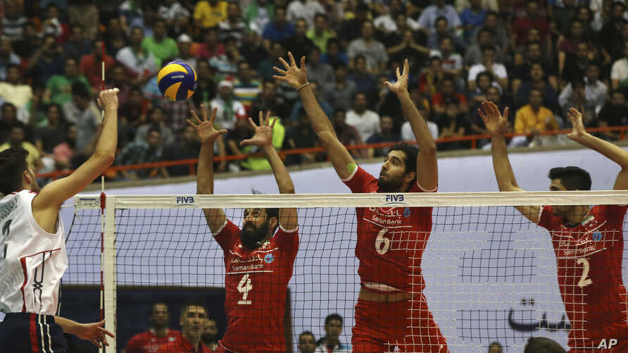 USA volleyball player Aron Russell, left, smashes the ball against, from left,  Iran's Mir Saeid Marouflakrani, Mohammad Mousavi Eraghi and Milad Ebadipour Ghara during Men's Volleyball World League, at the Azadi (Freedom) stadium in Tehran, Iran, Ju