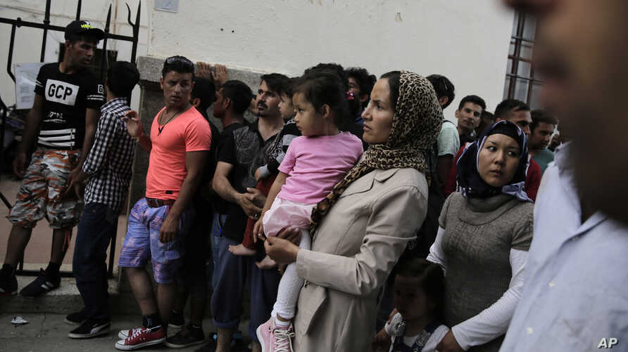 Immigrants wait outside a police station to receive temporary traveling papers at Kos island, Greece, May 27, 2015.