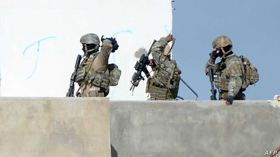 Members of the Tunisian military walk on a balcony during an operation against gunmen in the town of Oued Ellil near the Tunisian capital Tunis, Oct. 24, 2014.