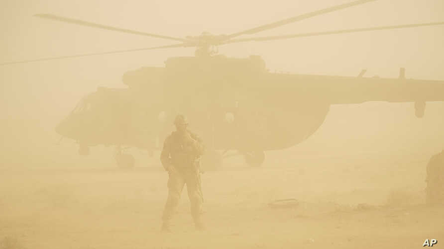 A Russian soldier stands guard as a military helicopter takes off at an airport in Deir eI-Zor, Syria, Sept. 15, 2017.