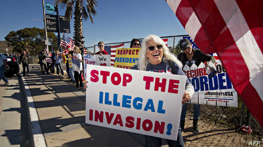 """Demonstrators chant during an """"America First"""" rally at the San Ysidro Port of Entry along the United States-Mexico border in San Ysidro, California, December 15, 2018."""