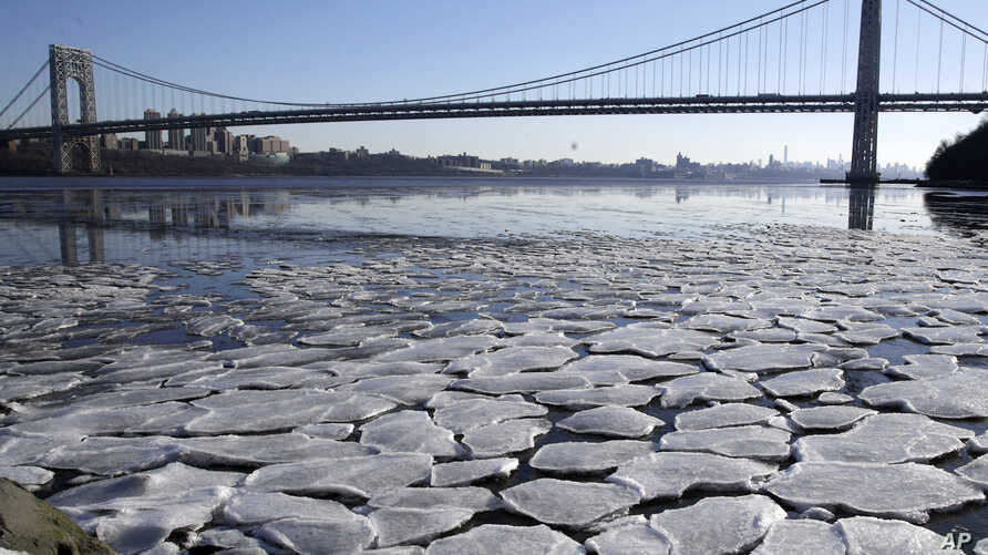 A layer of ice is broken into pieces floating along the banks of the Hudson River at the Palisades Interstate Park with the George Washington Bridge in the background, Jan. 2, 2018, in Fort Lee, New Jersey.