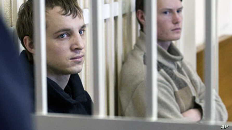 Leader of the Young Front opposition group Dmitry Dashkevich (l) and opposition activist Eduard Lobov during a court hearing in Minsk, March 24 2011