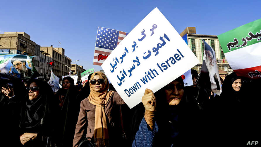 Pro-government demonstrators hold banners during a march in Iran's southwestern city of Ahvaz on Jan. 3, 2018, as tens of thousands gathered across Iran in a massive show of strength for the Islamic rulers after days of deadly unrest.
