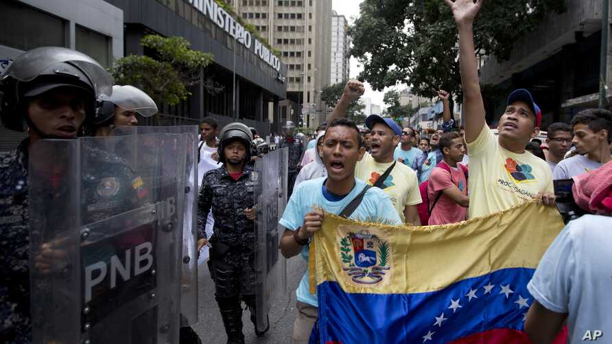 Opposition leader Leocenis Garcia, right, with members of his party, shout slogans against Venezuela's President Nicolas Maduro outside the attorney general's office, where police stand guard, in Caracas, Venezuela, July 18, 2018. The previous night,...