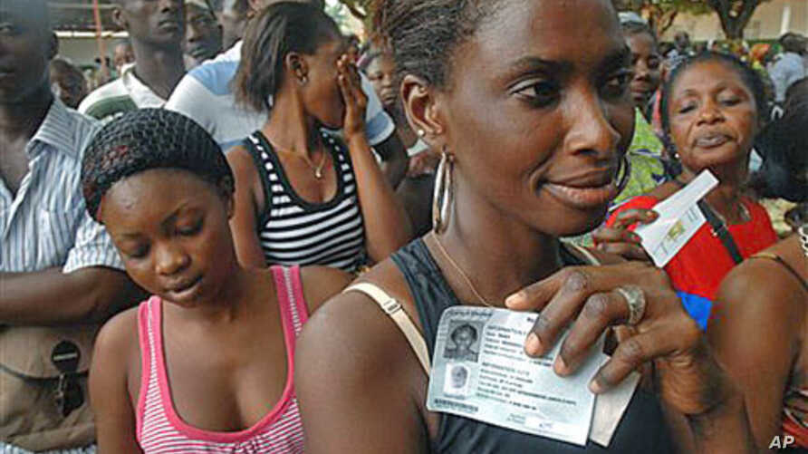After receiving their voter ID cards, local residents wait in line to claim their newly-issued national identity cards in the Plateau neighborhood of Abidjan, Ivory Coast, 7 Oct  2010