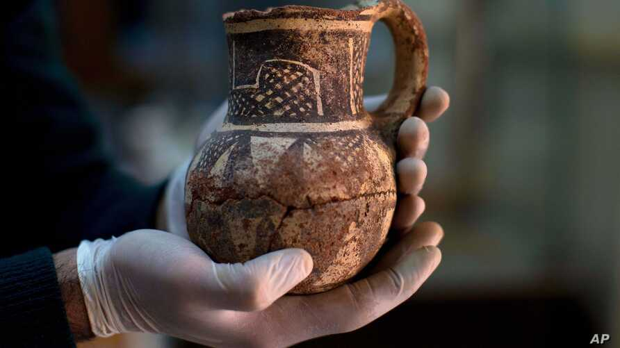 Jihad Abu Kahrlah, an archeologist at Syria's National Museum, holds an artifact delivered from the Daraa Museum to Damascus, Syria, Feb. 23, 2016. Faced with the Islamic State group onslaught and destruction by looters, Syrian antiquities authoritie...