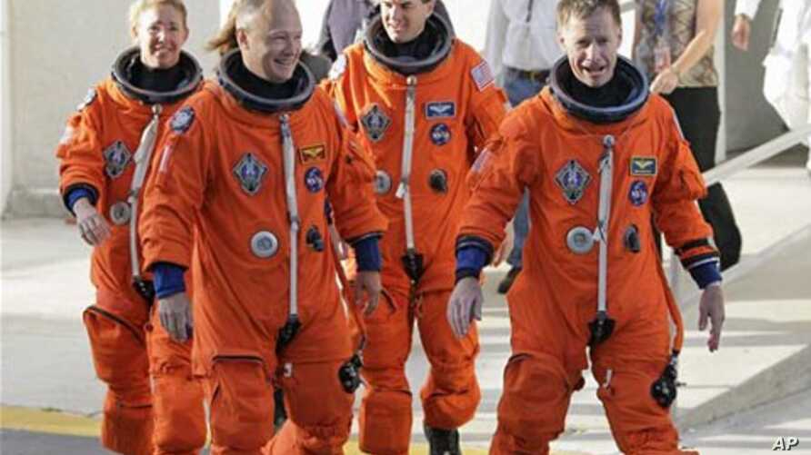 The crew of space shuttle Atlantis, from left, mission specialist Sandy Magnus, pilot Doug Hurley, mission specialist Rex Walhiem and commander Chris Ferguson,  leave the Operations and Checkout Building on their way to board the shuttle for their fi