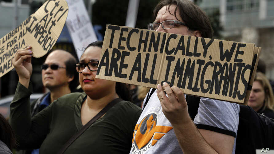 FILE - Tech workers hold signs as they protest Trump administration policies in San Francisco, California, Feb. 13, 2017.