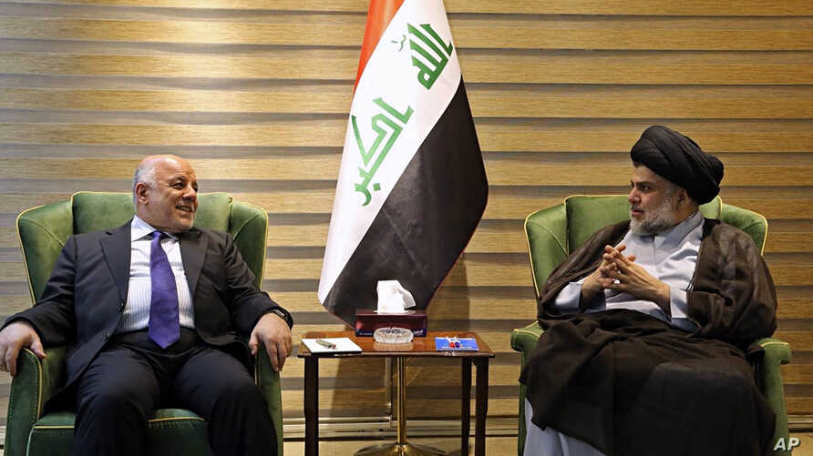 In this photo provided by the Iraqi government, Iraqi Prime Minister Haider al-Abadi, left, meets with Shiite cleric Muqtada al-Sadr in the heavily fortified Green Zone in Baghdad, May 20, 2018.