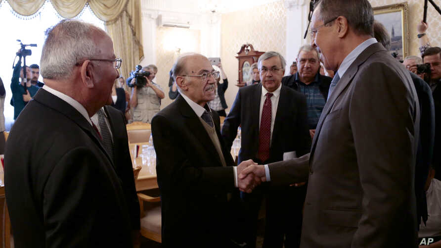 Russian Foreign Minister Sergey Lavrov, right, shakes hands with members of the Syrian delegation prior to a meeting with Qadri Jamil, former deputy prime minister representing Syria's opposition Popular Front of Change and Liberation, in Moscow, Aug
