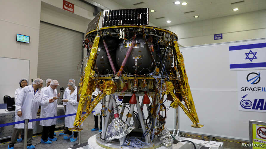 Israeli scientists stand next to an unmanned spacecraft which an Israeli team plans to launch into space at the end of the year and to land it on the moon next year, in Yahud, Israel, July 10, 2018.