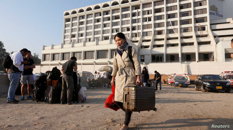 A foreign guest carrying her belongings as she leaves after a fire erupted in a hotel early morning in Karachi, Pakistan, Dec. 5, 2016.