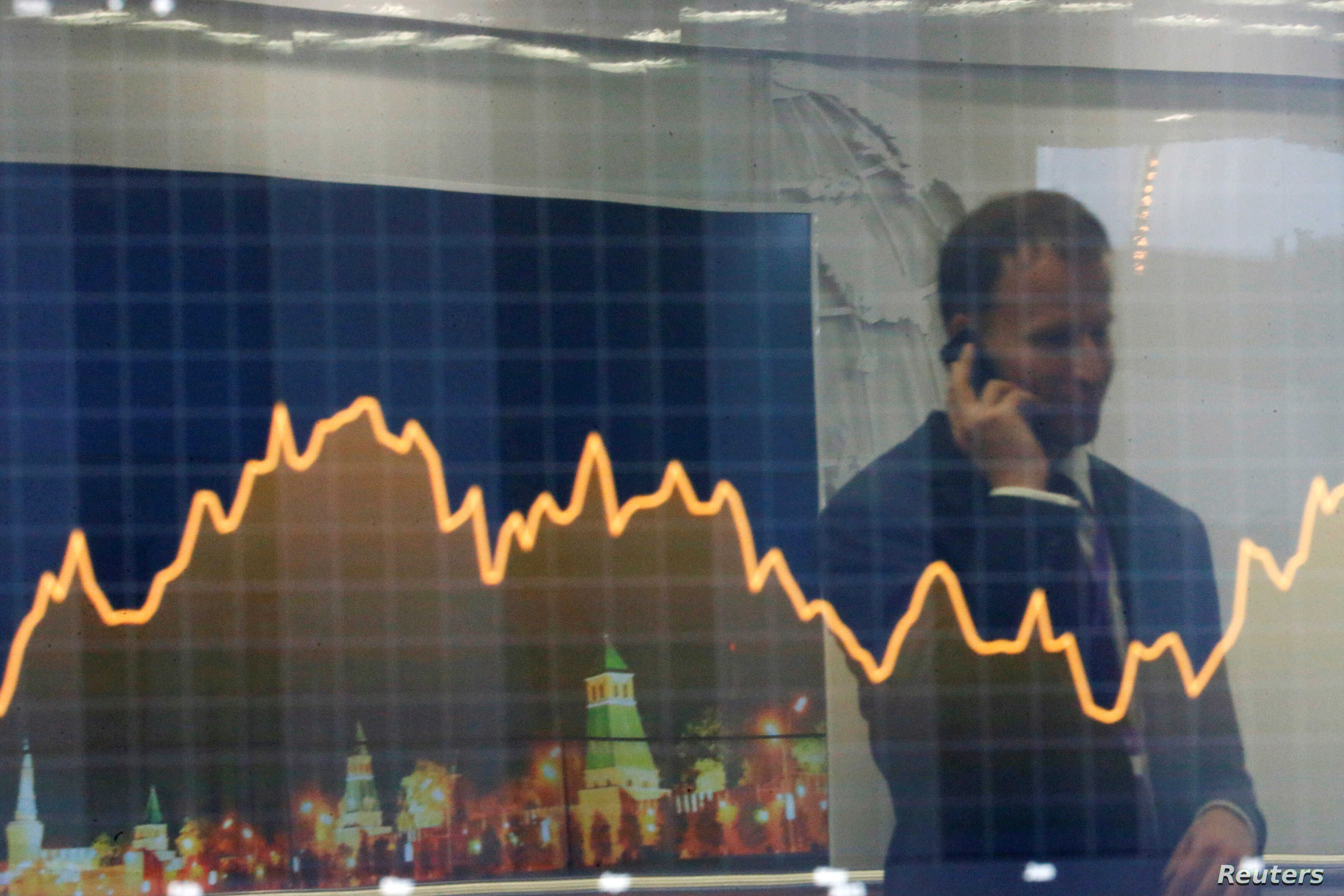 "FILE - A participant is reflected in a display showing business and financial information at the VTB Capital ""Russia Calling!"" Investment Forum in Moscow, Russia, Oct. 2, 2014."