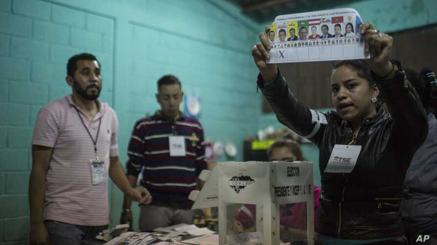 FILE - An electoral worker shows a ballot marked to Opposition Alliance presidential candidate Salvador Nasralla during the vote count in the general elections in Tegucigalpa, Honduras, Nov. 26, 2017.