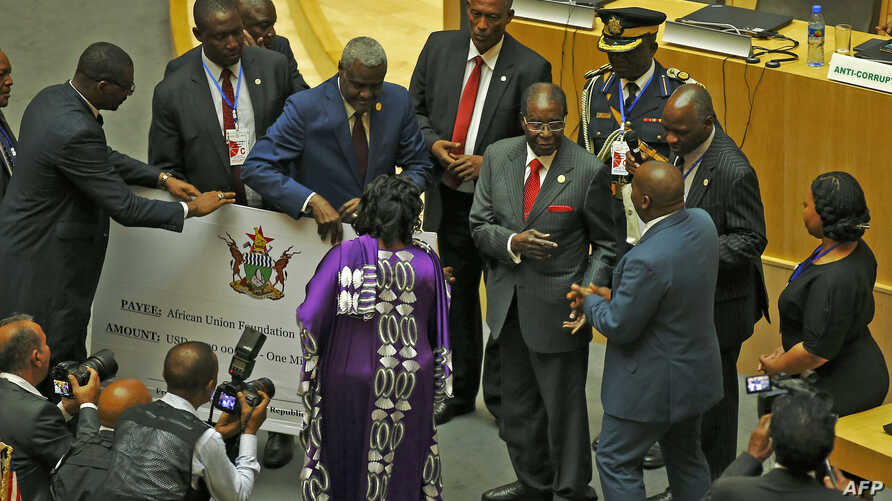 Zimbabwe's President, Robert Mugabe (C) gives a $1 million cheque to the African Union Foundation during the 29th African Union Summit in Addis Ababa, Ethiopia, July 3, 2017.