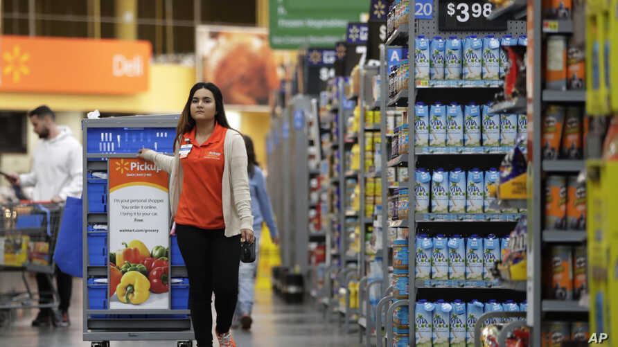 In this Thursday, Nov. 9, 2017, photo, Laila Ummelaila, a personal shopper at the Walmart store in Old Bridge, N.J., pulls a cart with bins as she shops for online shoppers.