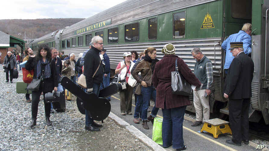 In this Saturday Nov. 7, 2015 photo, travelers board the Roots on the Rails music train in Bellows Falls, Vt. The special train made its first East Coast Trip between Bellows Falls and Rutland, Vt.