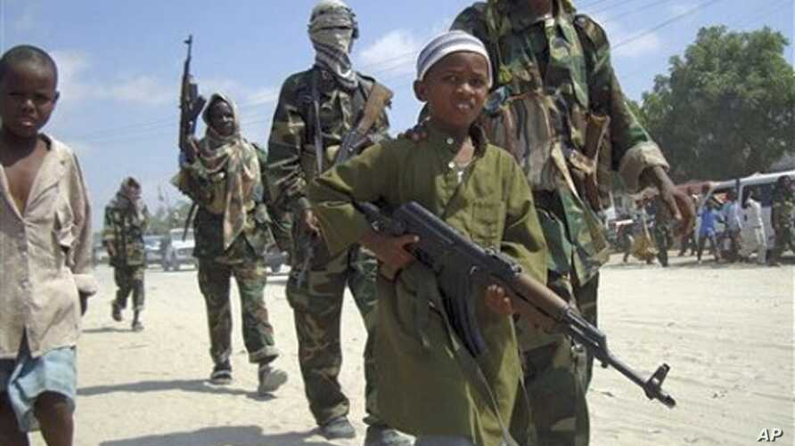 A young boy leads the hard-line Islamist Al Shabab fighters as they conduct military exercise in northern Mogadishu's Suqaholaha neighborhood, Somalia (File Photo)