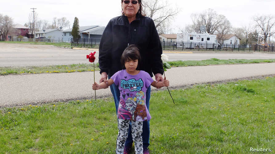 Delberta Seminole Eagleman stands with grandchild, 4-year-old Shawnee, whom she raises along with 5 others on the Fort Peck Indian Reservation, in Wolf Point, Montana, April 28, 2016.