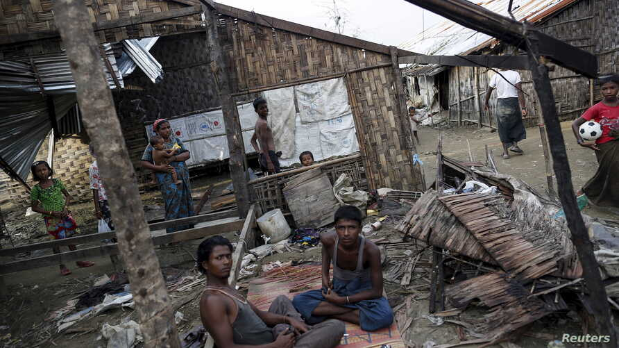 Rohingya people pass their time in a damaged shelter in Rohingya IDP camp outside Sittwe, Rakhine state on August 4, 2015