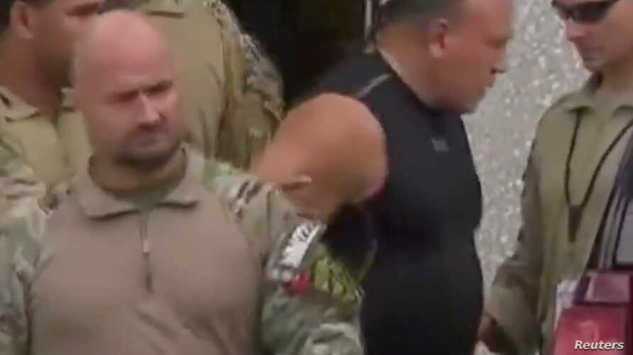 Cesar Sayoc, who was arrested during an investigation into a series of parcel bombs, is escorted from an FBI facility in Miramar, Florida, Oct. 26, 2018 in a still image from video.