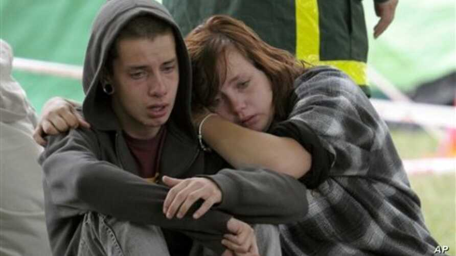 Kent Manning, 15, and Libby Manning, 18, wait for news of their mother who is trapped in the CTV building in Christchurch, New Zealand, after the city was hit by a 6.3 earthquake on Tuesday, February 23, 2011