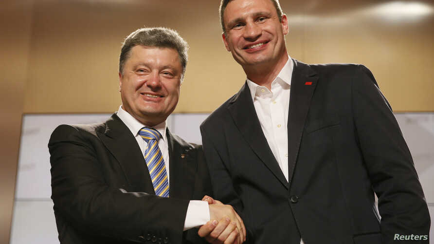 Ukrainian businessman, politician and presidential candidate Petro Poroshenko (L) and heavyweight boxing champion and Ukrainian Democratic Alliance for Reform party leader Vitali Klitschko shake hands during a rally at Poroshenko's election headquart