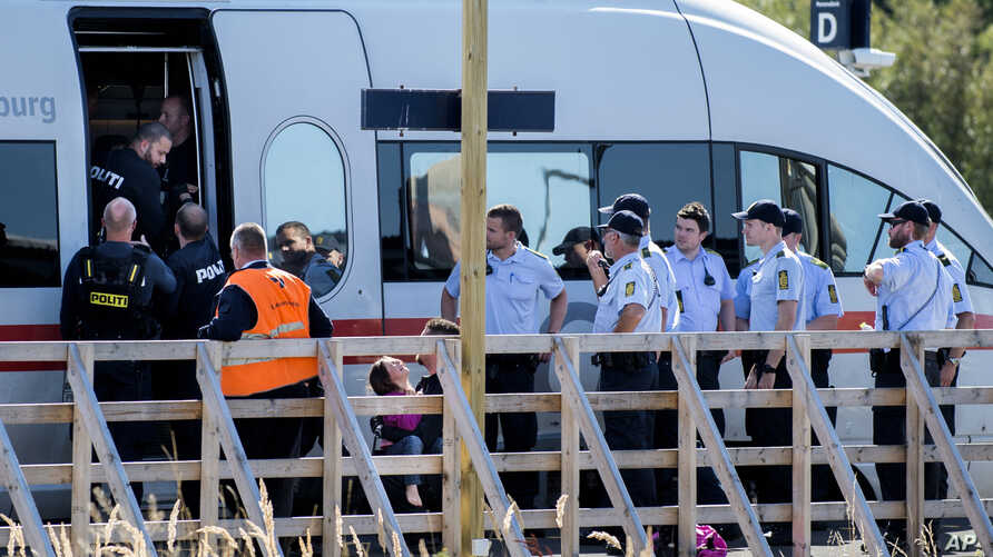 FILE - A small girl cries as she is removed by the police from an train in Rodbyhavn, approximately 5 km southwest of the town of Roedby, Denmark, Sept. 9, 2015.
