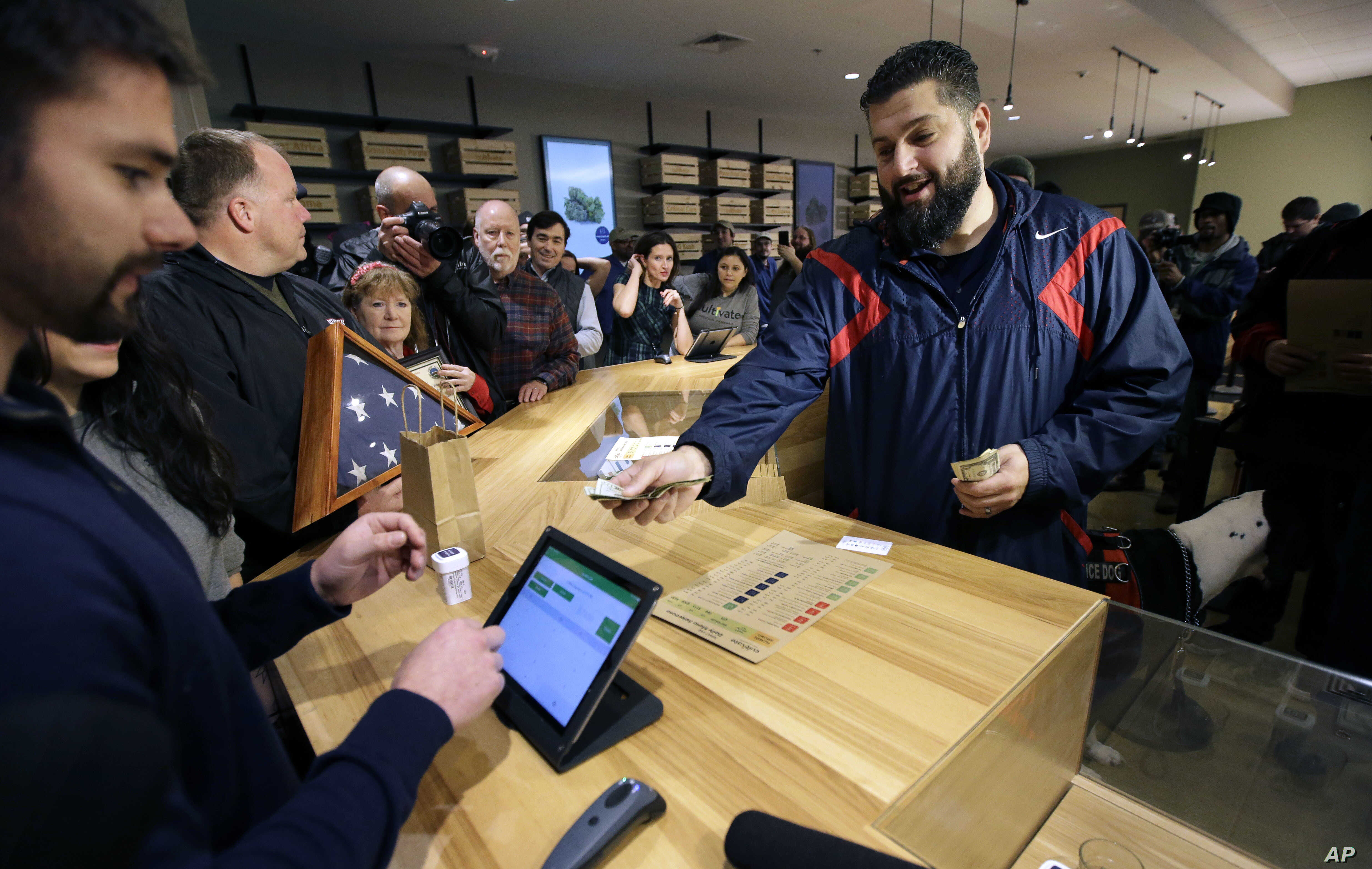 Stephen Mandile, right, an Iraq War veteran from Uxbridge, Massachusetts, is the first to purchase recreational marijuana at the Cultivate dispensary on the first day of legal sales, Nov. 20, 2018, in Leicester, Massachusetts.