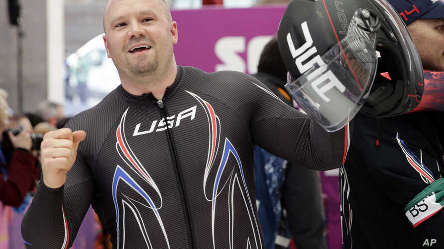 The driver of United States USA-1, Steven Holcomb, acknowledges the crowd after the team won the bronze medal during the men's four-man bobsled competition final at the 2014 Winter Olympics, Feb. 23, 2014, in Krasnaya Polyana, Russia.