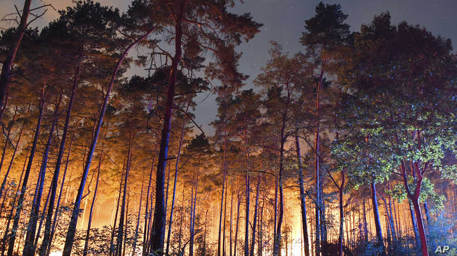 A fire burns in the forest near the German village of Klausdorf, about 85 kilometers (53 miles) south of Berlin on Aug. 24, 2018.
