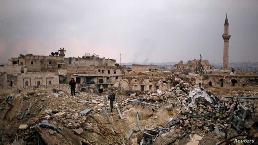 A member of forces loyal to Syria's President Bashar al-Assad stands with a civilian on the rubble of the Carlton Hotel, in the government controlled area of Aleppo, Syria, Dec. 17, 2016.