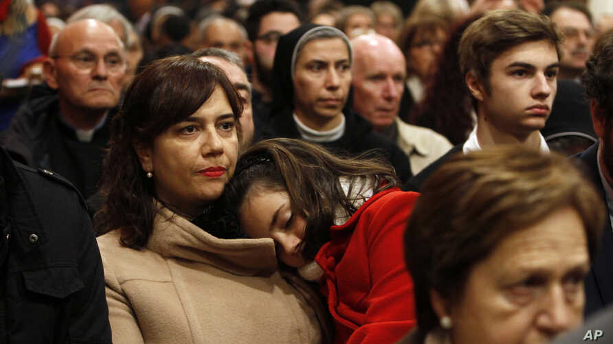 A Catholic worshiper carries her daughter as Archbishop Pierbattista Pizzaballa (not seen), apostolic administrator of the Latin Patriarch of Jerusalem, leads the Christmas Midnight Mass in Saint Catherine's Church at the Church of the Nativity, Dec.