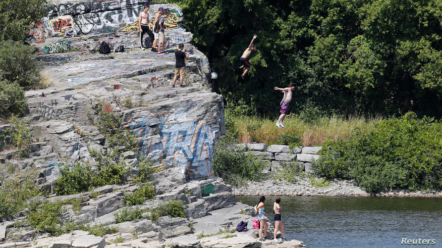 People jump into the Ottawa River on a hot summer day in Gatineau, Quebec, Canada, Aug. 10, 2016.