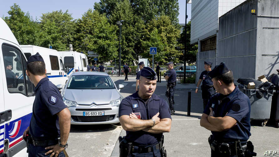 French policemen stand next to a police station on July 20, 2013 in Trappes, a suburb of Paris.
