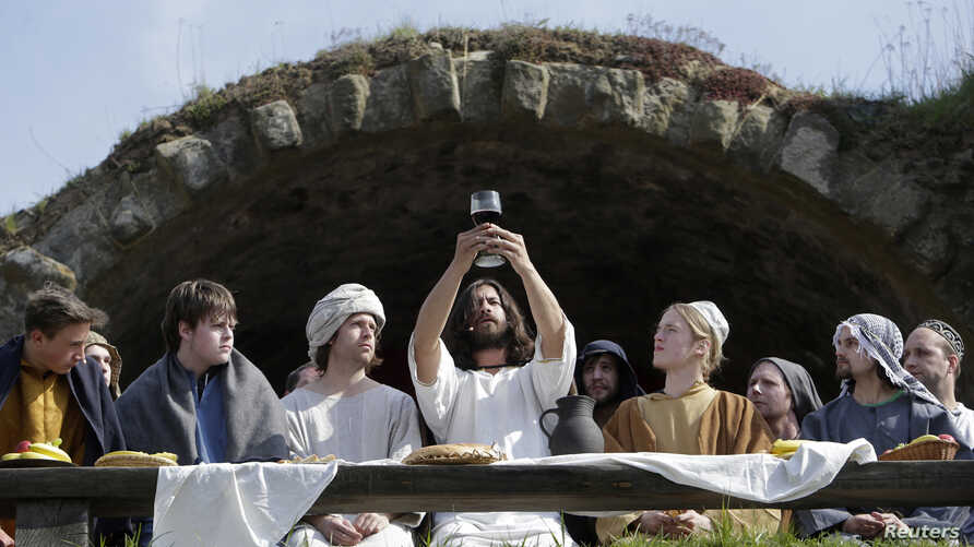 Actors raise a challice during a Last Supper recreation as part of Easter festivities in the Czech Republic city of Ceska Lipa April 19, 2014.