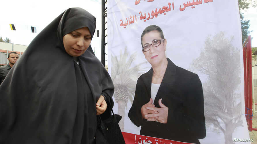 FILE - A women walks past electoral posters of Louisa Hanoune, a candidate for Algeria's Workers' Party in the 2014 presidential election, March 27, 2014.