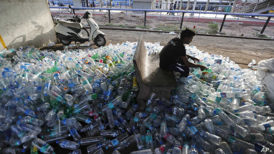 IAn Indian worker sorts used plastic bottles before sending them to be recycled, at a railway station on World Environment Day in Ahmadabad, India, June 5, 2018.
