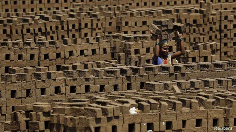 A laborer carries bricks at a kiln in Karjat, India, March 10, 2016. Thousands of brick kiln workers in India's western Maharashtra state are learning from activists that they have the right to a minimum wage, basic amenities and fair treatment - but