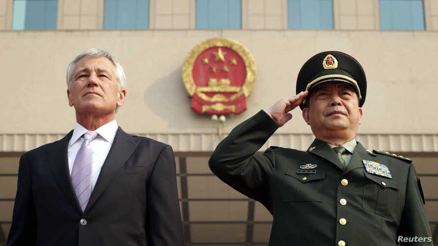FILE - US Defense Secretary Chuck Hagel (L) and his Chinese counterpart Chang Wanquan (R) listen to the Chinese national anthem during a welcoming ceremony at the Chinese Defense Ministry headquarters, prior to their meeting in Beijing, April 8, 2014
