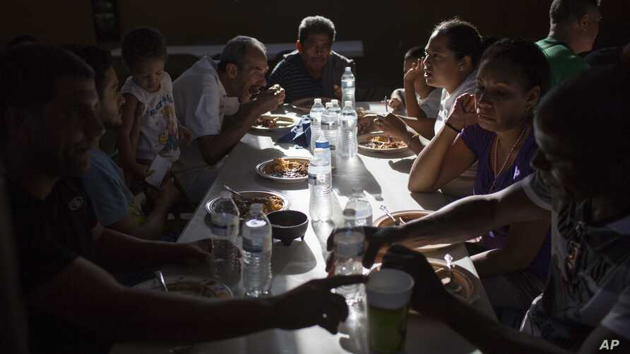 """Cubans eat dinner, March 25, 2017, at the migrant shelter """"Casa del Migrante"""" in Nuevo Laredo, Mexico, across the border from Laredo, Texas. Some Cubans have been stuck here since then-President Barack Obama on Jan. 12 ended the so-called """"wet foot,"""