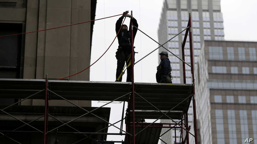 FILE- Construction workers work in midtown Manhattan in New York, Feb. 20, 2018.