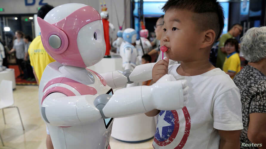 FILE - A boy stands next to an iPal robot at Avatarmind's booth at the World Robot Conference (WRC) in Beijing, China,.