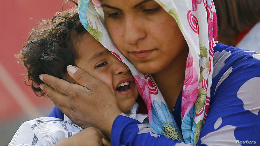 A Syrian Kurdish refugee woman and her child wait after crossing the Turkish-Syrian border near the southeastern town of Suruc in Sanliurfa province, Sept. 27, 2014.
