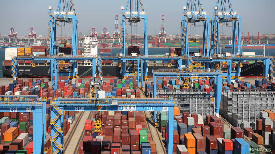 A cargo ship is seen behind containers at an automated container terminal in Qingdao port, Shandong province, China, Oct. 1, 2018.